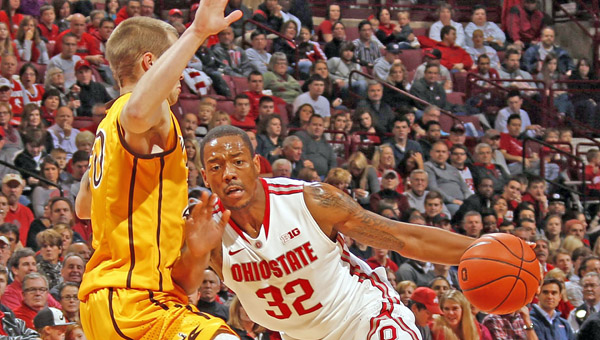 Ohio State Buckeyes guard Lenzelle Smith Jr. (32) drives past Wyoming Cowboys guard Nathan Sobey (20) during the first half at Value City Arena in Columbus on Monday. (MCT Direct Photo)