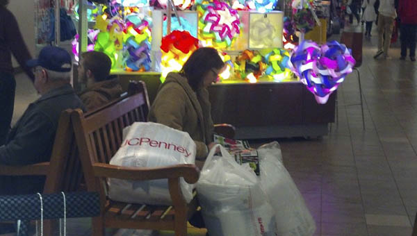 A Black Friday shopper rest on a bench inside the Ashland Town Center Mall. Photo by: The Tribune/Justin Prince