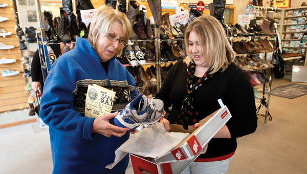 Crystal Schwab, right, is seen assisting Diane Moresea, left, while shopping at Unger's Shoes in downtown Ironton, during Small Business Saturday.