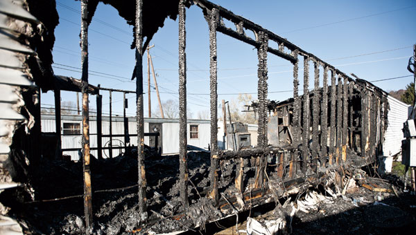 A neighboring trailer can be seen through the charcoaled remains following an early morning fire that destroyed a mobile home in the Sheridan Area. No injuries were reported.