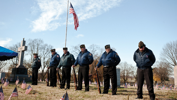 Members of VFW Post 8850 stand with their heads bowed during a benediction given by Chad Pemberton during the annual Veterans Day service at Woodland Cemetery.