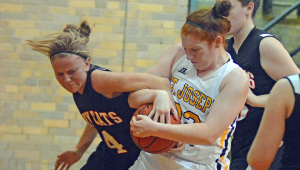 St. Joseph Female Flyers center Bri Bridges (right) fights to take a rebound from Whiteoak's Emily Stratton (4) during a 57-44 win Thursday. (Kent Sanborn of Southern Ohio Sports Photos)