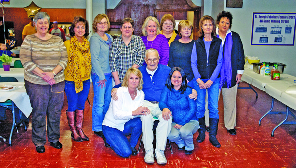 The St. Joseph Female Flyers basketball teams from the early 1970s who were among the first girls' programs in the state of Ohio. The school hosted a reunion for those teams with several former players attending last Saturday. Pictured are: front row left to right, Sheila (Kline) Gagai, coach B.J. Hannon and mascot Jessie (Hanson) Basham; standing from left to right, Barb Lutz, Kathy (Roadcup) Crawford, Mary Ann (Holmes) Newhouser, Sherri Malone, Jane (Hacker) Laber, Mariclare (Bowen) Waginger, Barb Holmes, Andrea (Waginger) Harvey and Terri Hannon.