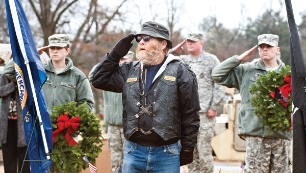 Jim Kelly stands at attention during the playing of the national anthem at the Wreaths Across America ceremony Saturday at Woodland Cemetery.