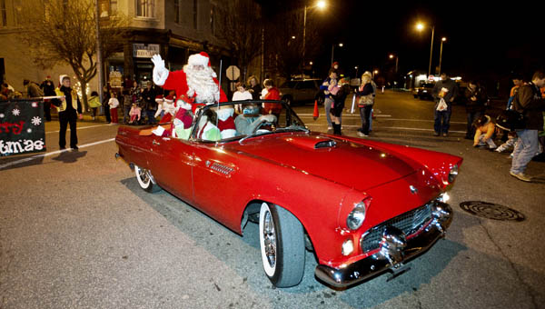 Santa Claus makes his way down South Third Street to the end of the Ironton Christmas Parade Monday evening in downtown Ironton. This year Mike Carey, owner of the Thunderbird, received the Appreciation Award for use of his car that has carried Santa since 1998.