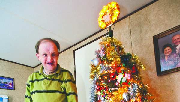 Keith Boggs, of Pedro poses next to one of two Christmas trees inside his home.