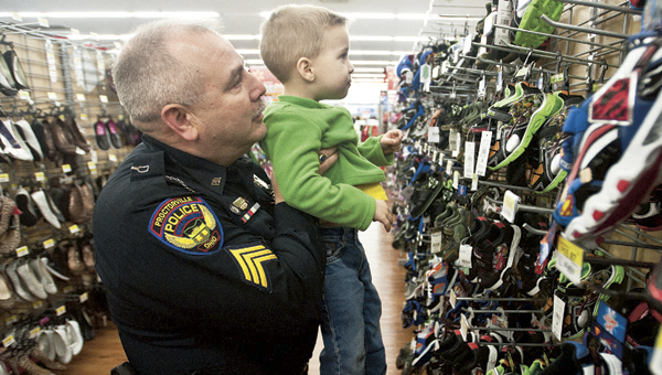 Officer Randy Thompson, with the Proctorville Police Department, gives little Acy Allen, 3, a lift to get a better look at a pair of shoes during the Shop with a Cop event at Wal-Mart Monday evening. Over 45 area children took part in the event.