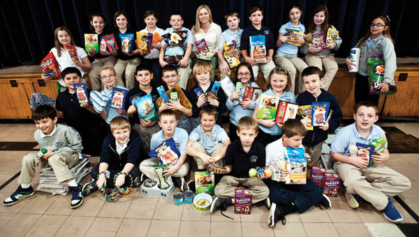 Students from St. Lawrence Schools fourth grade class are seen holding a variety of donated items from dog and cat food to blankets to be given to the Lawrence County Animal Shelter.