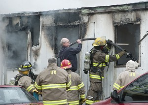 Chief Runyon is seen assisting Ironton fire fighters at a trailer fire located at the Sta-Tan Trailer Park Friday afternoon.