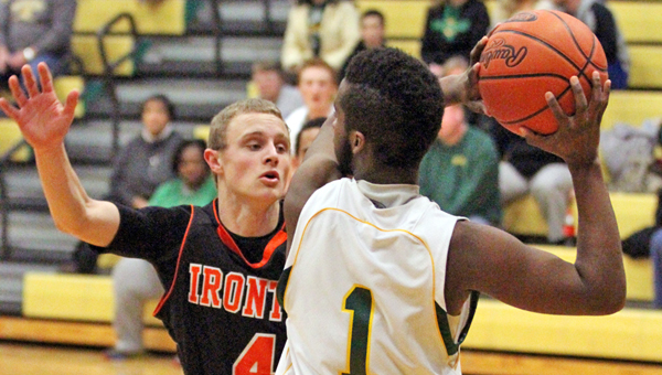 Ironton Fighting Tigers' Phillip Kratzenberg (4) applies defensive pressure to Greenup County's Jherrell Jackson (1) during Monday's game at Lloyd, Ky. The Musketeers managed to beat the Fighting Tigers in overtime, 63-57. (Courtesy Tim Gearhart of Tim's News & Novelties in Ironton)