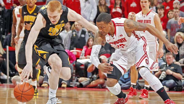 Ohio State Buckeyes guard Lenzelle Smith Jr. (32) can't come up with the steal against Iowa Hawkeyes forward Aaron White (30) during the 2nd half of their game at Value City Arena in Columbus on Sunday. The Buckeyes lost to Iowa, their second straight game. (MCT Direct Photo)
