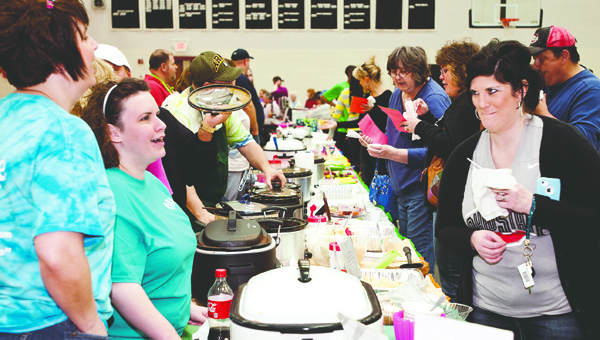The Tribune/Jessica St. James (ABOVE) Chili aficianadoes test the recipes of cooks participating in the Board of DD chili fest. Month. This year will be the 15th annual festival that brings out cooks from across the Tri-State.
