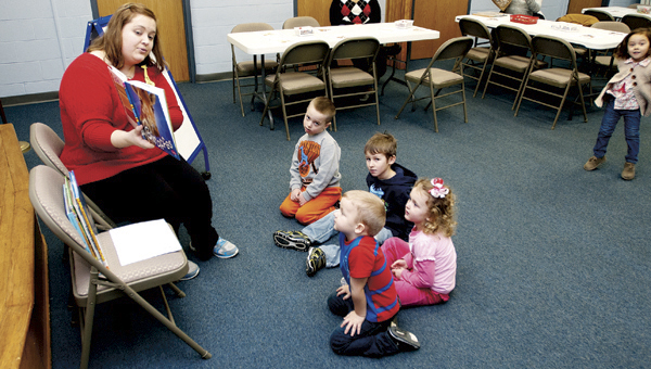 THE TRIBUNE/JUSTIN PRINCE Jane Gullet reads a story about giraffes to a group of preschools at Briggs Library.