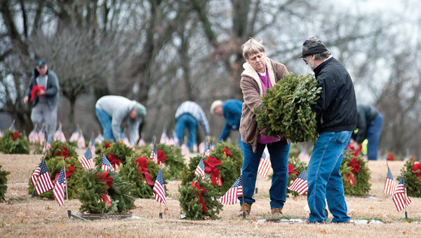 Volunteers remove the holiday wreaths from soldiers' graves at Woodland Cemetery on Saturday. The greenery was placed in December as part of Wreaths Across America.