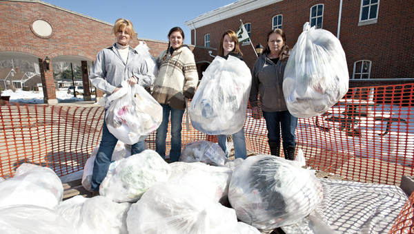 THE TRIBUNE/JESSICA ST JAMES Ohio University Southern students Patty Young, Sarah Simmons, Valerie Windhorst and Gayle Roberts, pictured left to right, display the amount of garbage generated in just one day by students and faculty at the school.