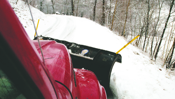 """While most people avoid driving in hazardous conditions, employees of the Lawrence County Road Department strap on boots and head out the door. """"It looks really bad and driving is dangerous but because it's wet and heavy it's an easy type of snow to plow,"""" Don Wilson, road department superintendent, said. """"It takes each man seven or eight hours to do his entire route."""" Eleven four-ton trucks — each equipped with a nearly two-ton plow in the front and 10 or so tons of a salt and grit mix in the back — take to the 380 miles of county roads well before daylight to make commuters' drives as safe as possible. The fleet also includes two graders.  Each driver has a dedicated route of nearly 40 miles, but total distance traveled doubles when taken into account routes have to be driven twice so both sides are treated. """"Drivers start with the most traveled road of their routes and work toward the least traveled,"""" Wilson said. """"We don't have the manpower or money to work around the clock. Some state crews were out at 10 p.m. last night and the roads they treated looked like they hadn't been touched this morning. We wait until the snow dies down, hit the roads hard and get them cleared. 11:50 a.m. — Deering resident Jay Jenkins finishes his lunch and prepares to depart the county garage to clear the least-traveled and most treacherous road on his route. This trip is the seven-year road department employee's fourth of the day. """"It's pretty, but that's about it,"""" Jenkins said about snow as he guided his modified International dump truck through the center of Coal Grove. """"I'd like to have one, maybe two snows a year and then I'm good with it."""" 12:01 p.m. — Jenkins, 48, takes the good with the bad when doing snow removal. He turned onto the narrow, curvy, up-and-down County Road 55 and lowered his plow. """"This kind of snow just peels right up,"""" he said. """"The temperature being right at freezing makes it easier, too."""" The warmer temperatures, Jenkins said, aid the road-clearing proce"""