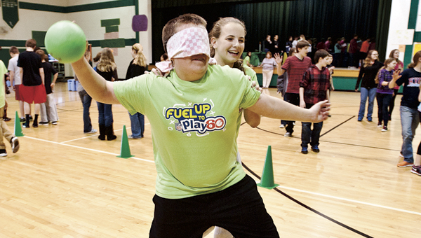Kelsie Warnock leads Michael Jeffrey around in a game of Tank, a variation of blind man's bluff, at the Fairland Middle School Fitness Fair Friday.  THE TRIBUNE/JESSICA ST JAMES
