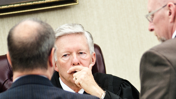 udge Charles Coopers convenes in a sidebar with attorneys Brigham Anderson, left, and Mike Davenport, right.