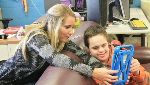 Rock Hill High School senior and National Honor Society member Allison Schwab tutors student Nathan Welch about features on one of the new iPads for the school's Multi-handicapped Classroom purchased with money obtained from a grant written by Schwab.