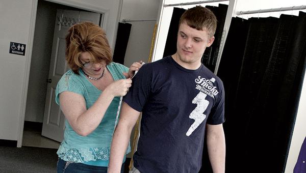 THE TRIBUNE/JESSICA SAINT JAMES   Ferguson assists David Abrams with a tuxedo fitting.
