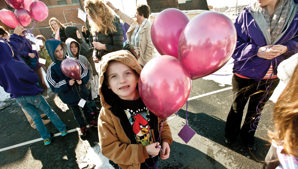 James Hall waits anxiously for the annual balloon launch at Open Door School. (BELOW) Students and faculty let their balloons fly.