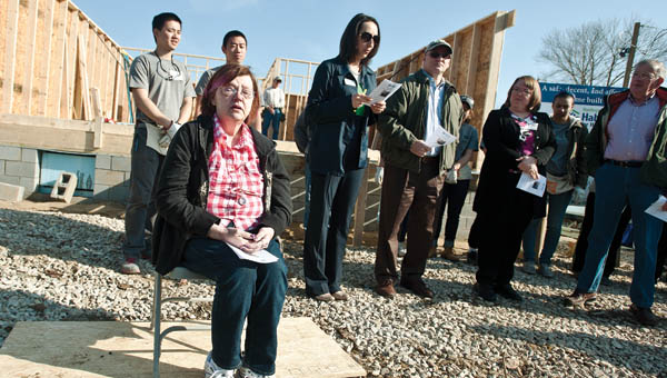 """Linda Dennison, seated, holds back the tears as Gary Prater performs the song """"Habitat, It's You and It's Me"""" during a wall-raising ceremony in Miller on Friday."""