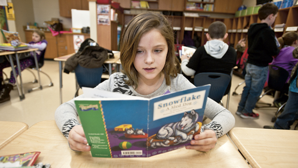 "Matti Hapney enjoys the book ""Snowflake a Sled Dog."""
