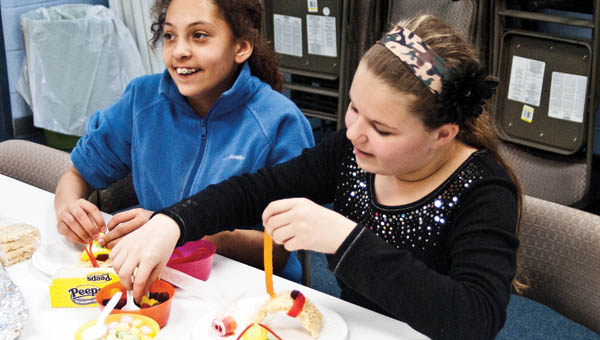 Students try their hand at making candy sushi.
