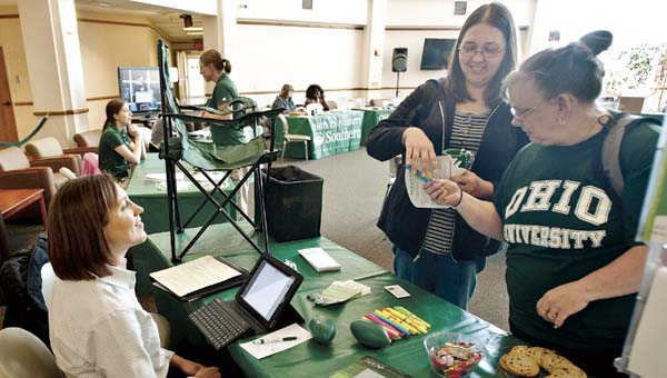 Roxann Gool, left, and Cheryl Hamilton, right, speak with Eva Bloom with Ohio University Credit Union during the grad fair in the school's Mains Rotunda.