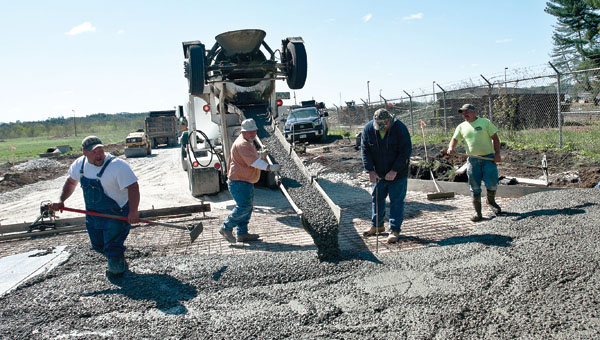 Employees from Mullins Construction lay cement at the new entrance, located along Sixth and Lorain streets.