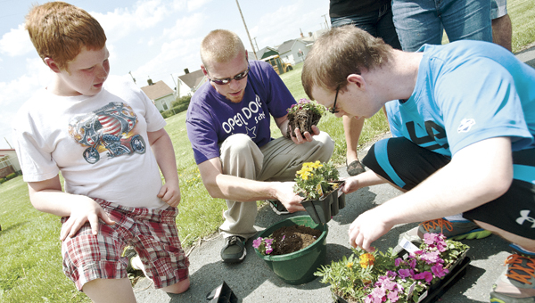 THE TRIBUNE/JESSICA ST JAMES (ABOVE) Students J.T. Jones, left, and Tyler Brown, right, work with Open Door School faculty member Curt Brady, center, as they plant flowers in pots as part of an Arbor Day project.