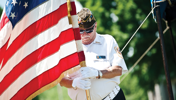 Bennie Blankenship held the American flag with his head bowed during the invocation at the Veterans Memorial Service at Woodland Cemetery Sunday afternoon.