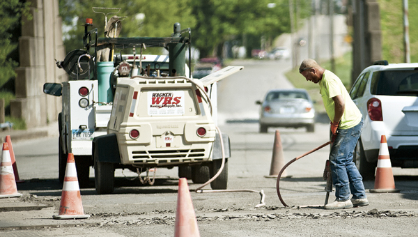 THE TRIBUNE/JESSICA ST JAMES Steve Lemay, with Allard Construction, uses a jackhammer Tuesday on North Second Street at the floodwall while traffic passes by.