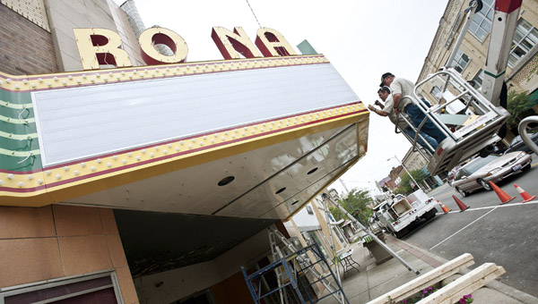 the tribune/jessica st. james Employees from Paris Signs, of Huntington, W.Va., install the marquee Ro-Na marquee Wednesday in downtown Ironton.
