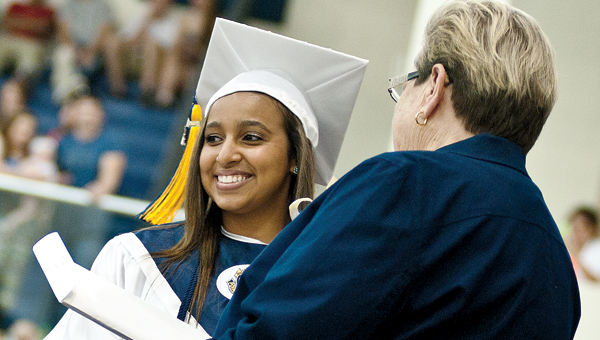 ) Miranda Clair-Kay Lenease Lewis receives her diploma during commencement ceremonies Sunday at South Point High School. (BELOW) Austin Shaffer talks with friends at South Point High School Sunday afternoon.