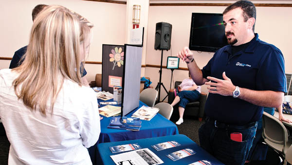 Mike Walker, with Air Evac Lifeteam, speaks with visitors to the Resource Fair Friday at Ohio University Southern.