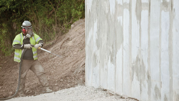 An employee with Twin Rivers Construction Co., of Marietta, air blasts the new retaining wall along Rockwood Avenue.