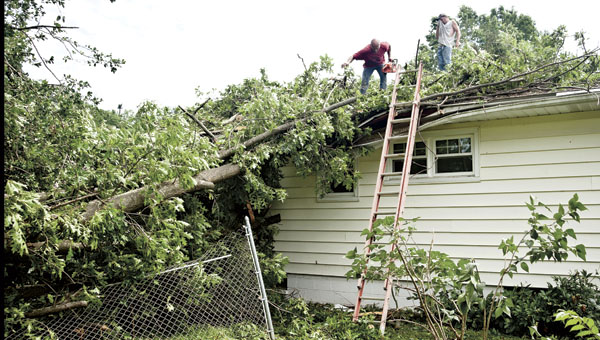 THE TRIBUNE/JESSICA ST JAMES Volunteers help out a neighbor as they remove a tree from the top of a home outside of Chesapeake Wednesday.