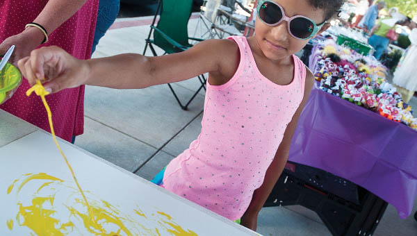 Seven-year-old Journey Blithe uses cooked spaghetti as her brush to create a painting while visiting the Ironton Farmers Market on Saturday.