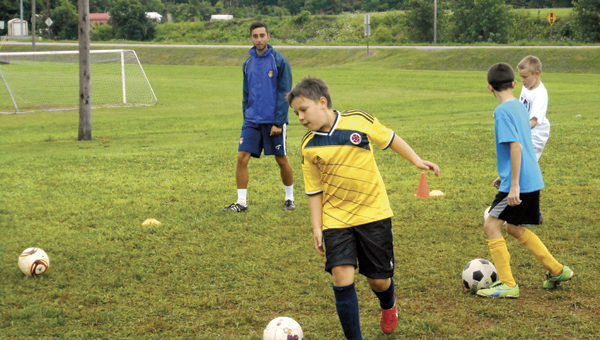 The Tribune/Justin Prince Coach Matt Wirnes looks on as players participate in a drill at the annual Challenger Sports Soccer Camp.