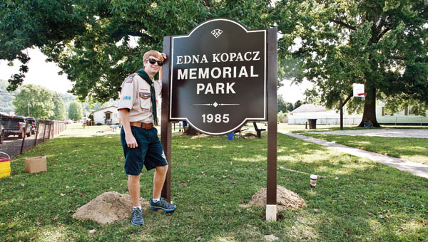 Andrew David McCown stands in front of the newly erected park sign at the Edna Kopacz Memorial Park on Saturday.