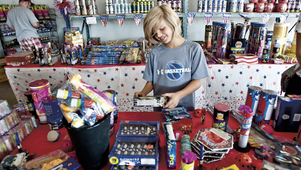 THE TRIBUNE/JESSICA ST JAMES Nine-year-old Whyatt Mannon looks through a selection of fireworks at Red White and Kaboom, located to the left off the Ashland bridge going into Ashland, Wednesday evening.