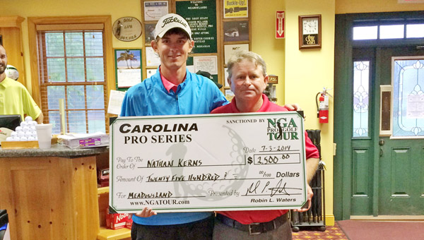Ironton's Nathan Kerns (left) proudly displays a replica of the first-place check he was presented after recording his first career professional victory Thursday in the NGA Tour. Kerns won the Meadowlands Tournament in the Carolina Series by two strokes with a nine-under par score. (Photo Submitted)