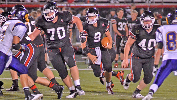 Coal Grove Hornets' senior offensive lineman Austen Pleasants (70) leads the blocking for Jesse Rigsby (9) on a quarterback keeper. Pleasants gave a verbal commitment to Ohio University on Wednesday. (Kent Sanborn of Southern Ohio Sports Photos)