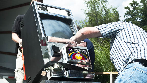 State and local law enforcement haul out Pot-o-Gold gambling machines following a raid at Sky Lake, a pay fishing lake in Chesapeake, Wednesday