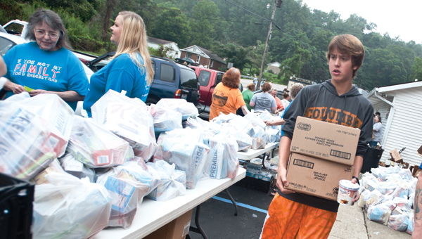 Josh Daniels carries boxes of food items during a food giveaway Saturday at Campbell Chapel Free Will Baptist Church.