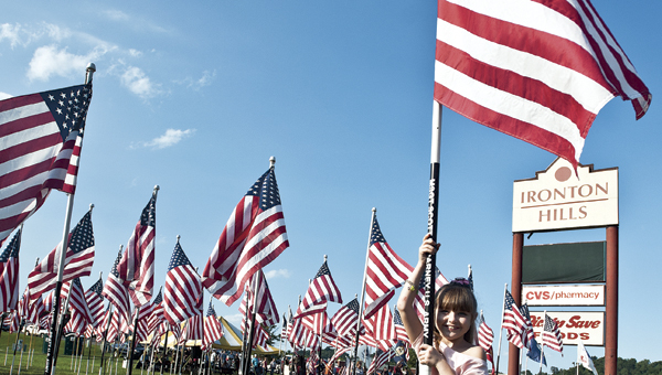 THE TRIBUNE/JESSICA ST JAMES Seven-year-old Sydney Henry helps set up flags, branded with the names of fallen soldiers and first responders from Ohio, during the Flags of Honor ceremony Thursday at the Ironton Hills Plaza.