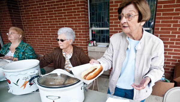 Kay Porter serves hotdogs during the annual Coal Grove Memorial United Methodist Church Block Party Saturday.