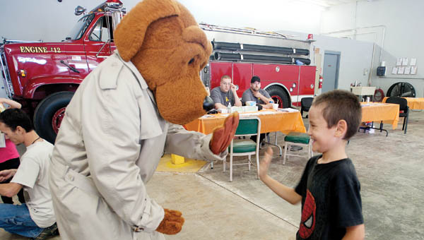 Seven-year-old Ayden Bayless gives McGruff the Crime Dog a high five during the Upper Township Fire Department Community Day event Saturday.