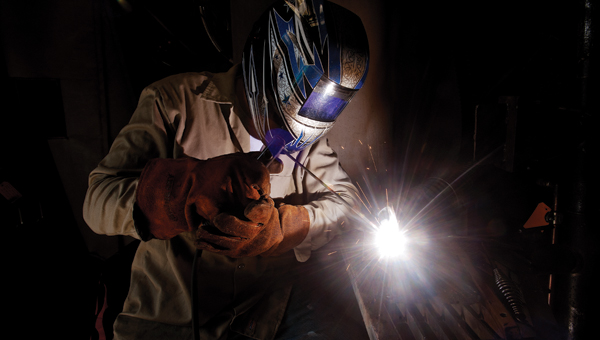 A ball of white light illuminates from the end of a welding torch while students practice welding techniques.